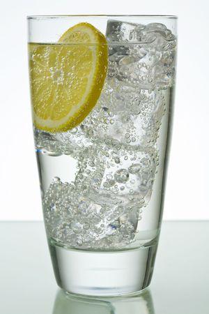 Bevanda frizzante in vetro con cubetti di ghiaccio e la fetta di limone  Archivio Fotografico