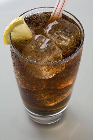 Glas cola met rietjes en ijs en citroen
