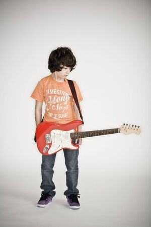 Young boy standing with an electric guitar