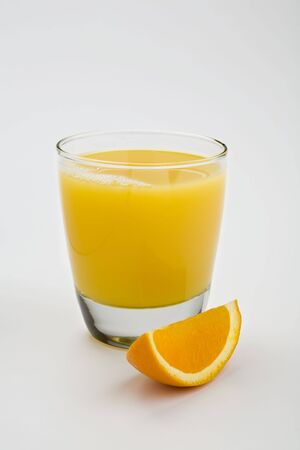 フォア グラウンドでオレンジ色のくさびとの白で隔離されるオレンジ ジュースのガラス