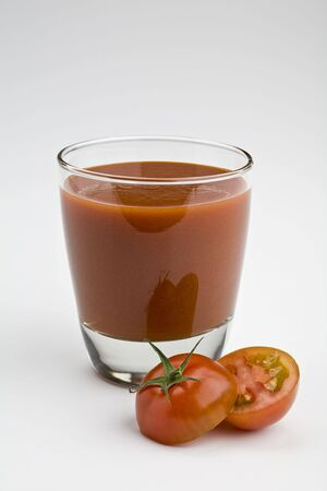 Glass of tomato juice on white with sliced tomato Imagens