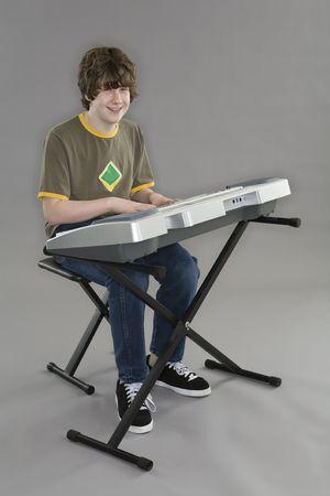 Tiener spelen en elektrische toetsen bord op een grijze achtergrond  Stockfoto