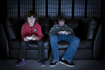 couches: Two boys sitting on a couch playing video games