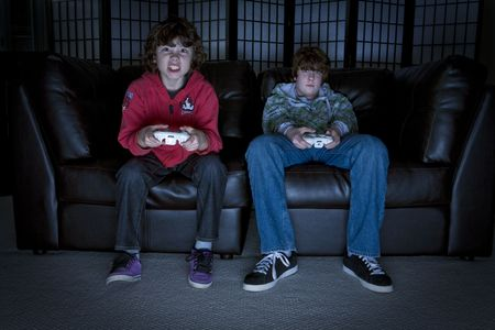 teens playing: Two boys sitting on a couch playing video games