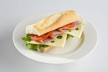 Ham en Zwitserse kaas baguette op witte plaat