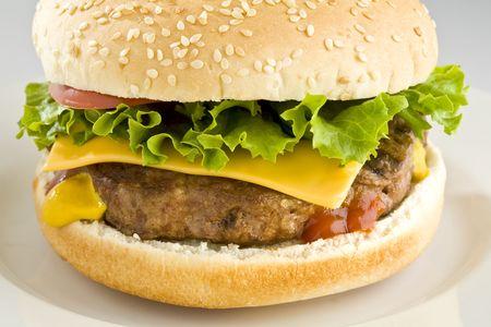 Cheeseburger met sla en tomaat op witte plaat Stockfoto
