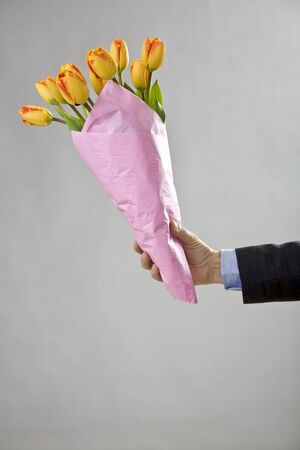 Mans hand holding a bouquet of orange tulips