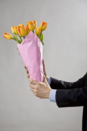 Mans two hands holding a bouquet of orange tulips