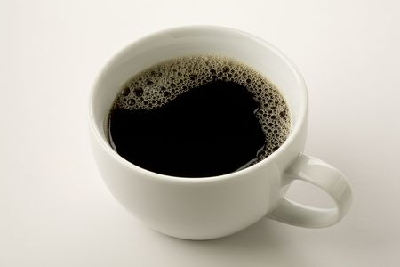 close up of black coffee in white cup with froth