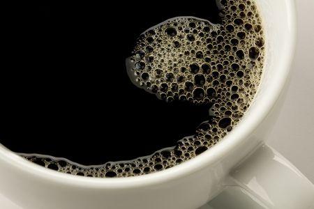 close-up van zwarte koffie in witte kop met schuim