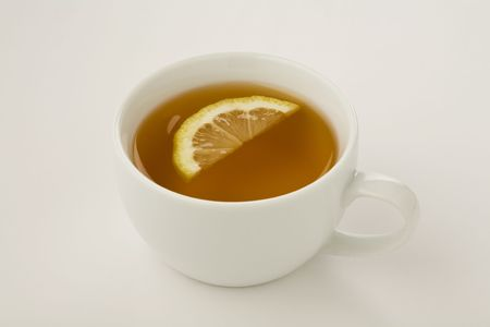 Cup of tea with a slice of lemon isolated on white Imagens