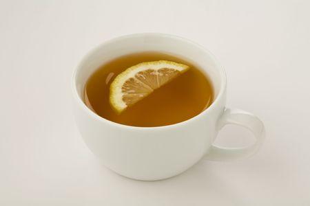 Kopje thee met een schijfje citroen geïsoleerd op wit