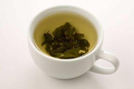 cup of green tea with leaves floating isolated on wite Imagens
