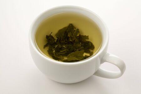 kop van groene thee met bladeren drijvend op geïsoleerde wite Stockfoto