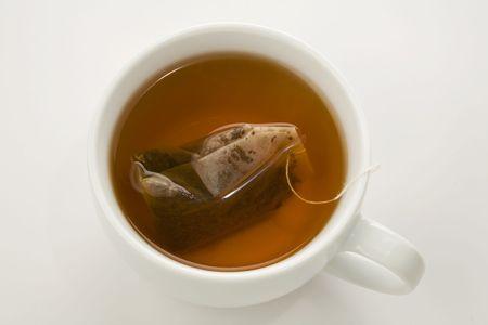 thee zakje brouwen in een witte kop geïsoleerd op wit