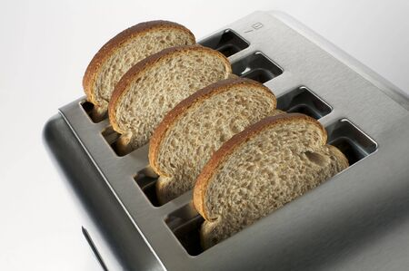 Four slices of brown bread in a stainless steel toaster Imagens