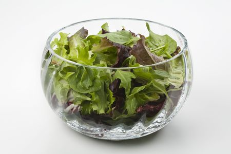 Mixed salad leaves in a glass bowl Imagens