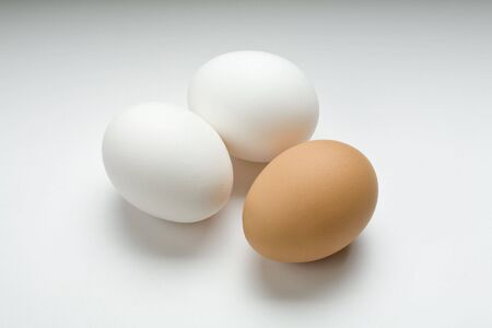Two white eggs and one brown egg on white Imagens