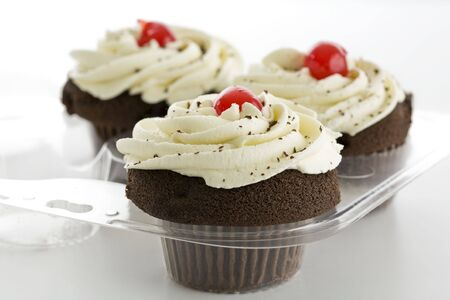 Three chocolate cupcakes with white frosting and red cherry Imagens