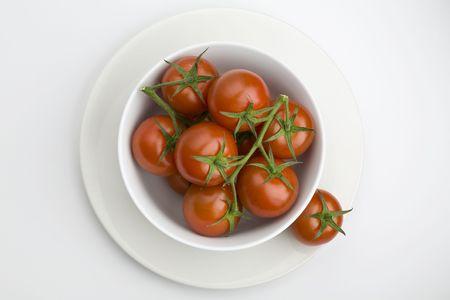Witte kom vol met wijn stok tomaten Stockfoto