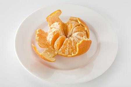 Mandarin orange partially peeled on white plate Imagens