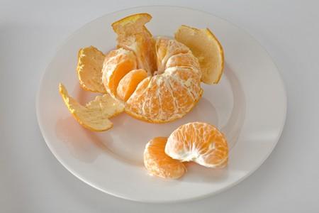 Mandarin orange partially peeled on white plate with two segments Imagens