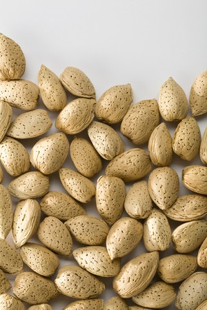 Whole unshelled almonds filling three quarters of frame