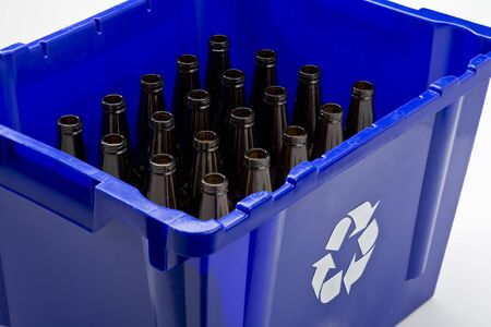 Blauwe doos met recycle symbool en lege flessen Stockfoto