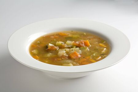 White bowl filled with vegetable soup on white