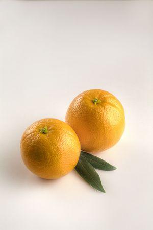 Twee kleine sinaasappelen met bladeren afgezonderd op wit
