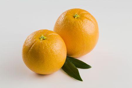 Twee hele sinaasappelen geïsoleerd op wit met horizont aal bladeren