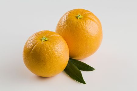 Two whole Oranges Isolated on White with Leaves Horizontal