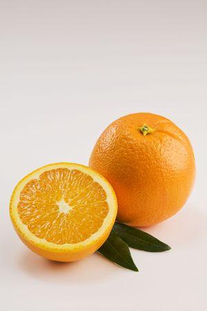 Een geheel en een halve sinaasappel geïsoleerd op wit met bladeren verticaal Stockfoto