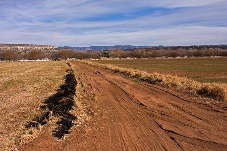 cutting through: A dirt road cutting through farm land. Stock Photo