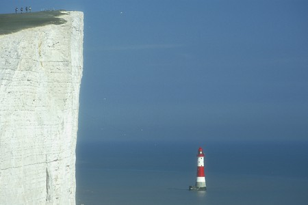 south downs: The lighthouse at Beachy Head. Four hikers on the South Downs Way.