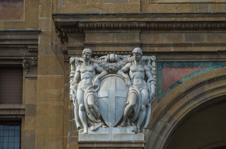 masonary: pair of white statues at side of historic archway entrance