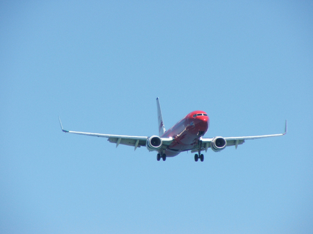 Jet airliner comming in to land with wheels down on a clean blue sky background