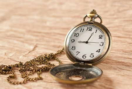 an old vintage pocket watch on grungy paper photo