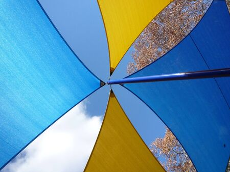 The Colorful  Beach Umbrella against a Background of Blue Sky and Clouds. photo