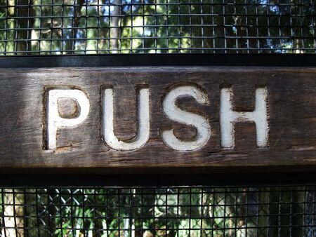 push: A wooden push sign panel  on door