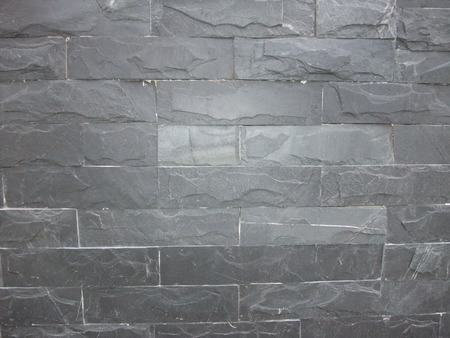 uneven: An uneven cracked real stone wall surface