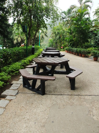 trimmed: Walk way with green trees, trimmed hedges, table and chairs Stock Photo