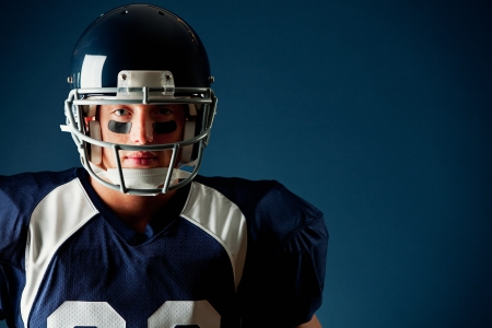 American football player, in uniform, on a blue background. Stock Photo