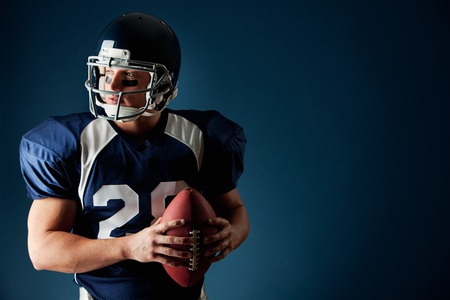 American football player, in uniform, on a blue background. Imagens