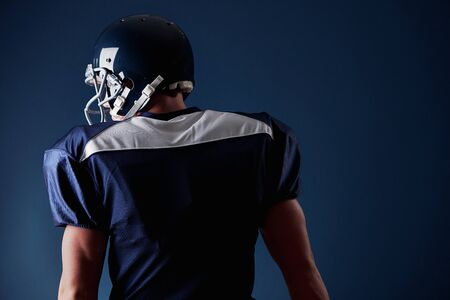 American football player, in uniform, on a blue background. Stok Fotoğraf