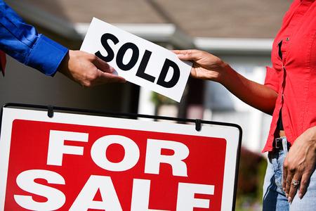 Uitgebreide reeks van een Kaukasische makelaar in onroerend goed en Afro-Amerikaanse echtpaar in de voorkant van een huis. Stockfoto