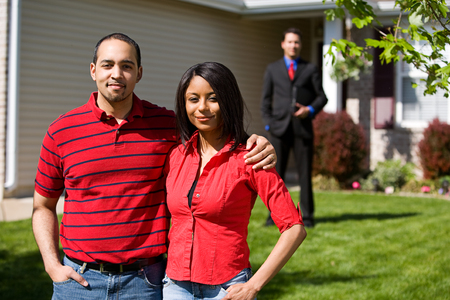 Home: Couple Stands In Front Of Home WIth Agent Stock Photo