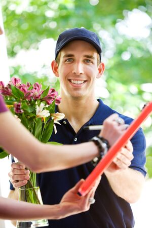 deliveryman: Delivery: Deliveryman Holds Clipboard Stock Photo