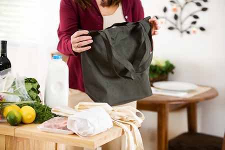 Reusable: Woman Shopper Folding Up Reusable Bags