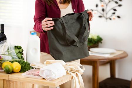 reusable: Reusable: Woman Shopper Folding Up Reusable Bags